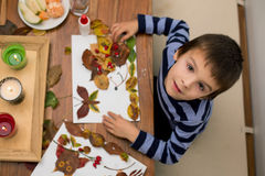 Sweet child, boy, applying leaves using glue while doing arts an Royalty Free Stock Photo