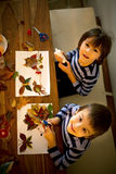 Sweet child, boy, applying leaves using glue while doing arts an Royalty Free Stock Photography