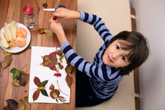Sweet child, boy, applying leaves using glue while doing arts an Stock Photos