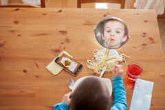 Sweet child, boy, having for lunch spaghetti at home, enjoying t Royalty Free Stock Image