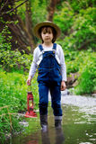 Sweet child, boy, holding red gas lamp, lantern. Standing in a river, looking for a way to go Stock Photo