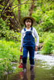 Sweet child, boy, holding red gas lamp, lantern. Standing in a river, looking for a way to go Royalty Free Stock Images