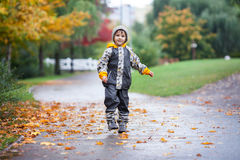 Sweet child, boy, playing in the park on a rainy day Royalty Free Stock Images