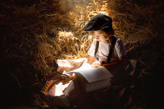 Sweet child, boy, reading a book on the attic on a house, sitting on a hay of straw. Eating bake rolls stock photos