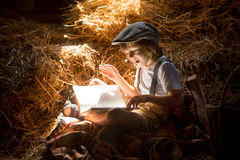 Sweet child, boy, reading a book on the attic on a house, sitting on a hay of straw. Eating bake rolls royalty free stock photo