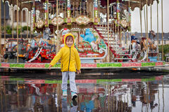 Sweet child, boy watching carousel in the rain, wearing yellow r Royalty Free Stock Images