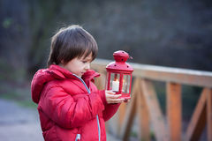 Sweet child, holding red lantern in the park on a sunny winter d Stock Image