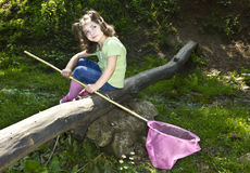 Sweet child holds butterfly-net in a park Royalty Free Stock Photography