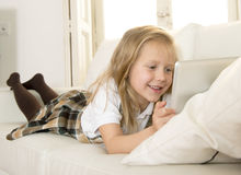 Sweet child lying on home sofa couch using internet app on digital tablet pad Royalty Free Stock Photography