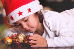 Sweet child plays with xmas tree balls Royalty Free Stock Image