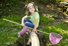 Sweet child sits on a dry branch above water Royalty Free Stock Photos
