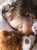 Sweet child sleeping with teddy bear Stock Image