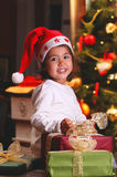 Sweet child smiles among Christmas gifts Stock Image