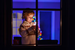 Sweet child standing by window at Christmas time and holding can Stock Photography