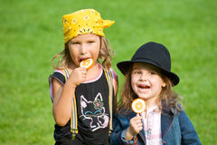 Sweet childhood. Two kids with lollipops in park Stock Photography