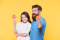Sweet childhood. Girl child and dad hold colorful lollipops. Sweets and treats concept. Daughter and father eat sweet. Candies. Sweet dessert. Bearded hipster stock image
