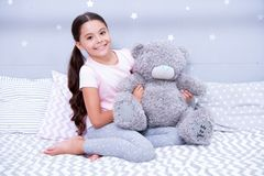 Sweet childhood. Girl child sit on bed with teddy bear in her bedroom. Kid prepare to go to bed. Pleasant time in cozy. Bedroom. Girl kid long hair cute pajamas stock photo