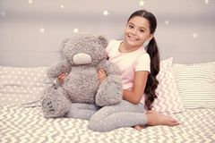 Sweet childhood. Girl child sit on bed with teddy bear in her bedroom. Kid prepare to go to bed. Pleasant time in cozy. Bedroom. Girl kid long hair cute pajamas stock images