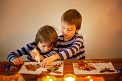 Sweet children, boys, applying leaves using glue while doing art stock photo