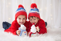 Sweet children, brother boys, playing with handmade snowmen at h. Ome, christmas lights behind them stock image