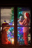 Sweet children, decorating christmas tree, impatiently waiting f Royalty Free Stock Photography