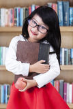 Sweet chinese schoolgirl in the library Royalty Free Stock Image