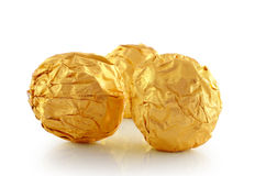 Sweet chocolate candy wrapped in golden foil Stock Photos
