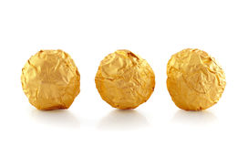 Sweet chocolate candy wrapped in golden foil Royalty Free Stock Photos