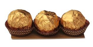 Sweet chocolate candy wrapped in golden foil. Isolated on white background Royalty Free Stock Image