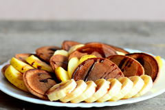 Sweet chocolate pancakes. Baked chocolate pancakes drizzled with caramel, fresh sliced bananas and apples on a plate Stock Photos