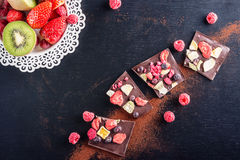 Sweet chocolate slices with fruits, cocoa powder and fruit on metal white plate. sweet dessert on black background Stock Photo