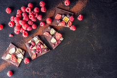 Sweet chocolate slices with fruits and cocoa powder. sweet dessert on black background Royalty Free Stock Photography