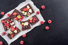 Sweet chocolate slices with fruits on white paper, sweet dessert on black backgroud. image for patisserie Royalty Free Stock Image