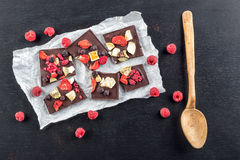 Sweet chocolate slices with fruits on white paper, sweet dessert with wooden spoon on black backgroud. image for patisserie Stock Photo