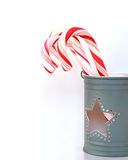 Sweet Christmas candy canes in a light gray cup with a star hole. Celebration, birthday and holiday concept Stock Images