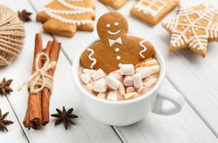 Gingerbread cookie man in cup of hot chocolate. Sweet Christmas composition. Gingerbread cookie in cup of hot chocolate on white table royalty free stock images