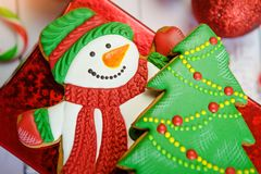 Festive Christmas Cookie and New Year in the shape of Christmas tree, snowman on wooden table background royalty free stock photos