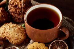 Christmas teatime with oatmeal, chocolate biscuits, and spices, on wooden background, close-up, selective focus. stock photo