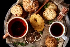 Christmas teatime with oatmeal, chocolate biscuits, and spices, on wooden background, close-up, selective focus. royalty free stock photography