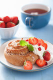 Sweet cinnamon roll with cream and strawberry for breakfast Royalty Free Stock Images
