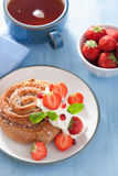 Sweet cinnamon roll with cream and strawberry for breakfast Royalty Free Stock Photography