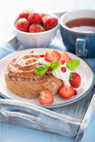Sweet cinnamon roll with cream and strawberry for breakfast Royalty Free Stock Photo