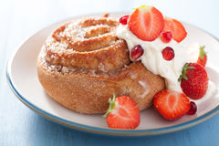 Sweet cinnamon roll with cream and strawberry  Royalty Free Stock Photo