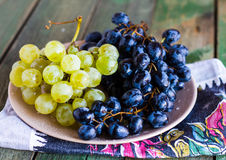 Sweet cluster of green and blue grapes on a plate Royalty Free Stock Photos