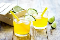 Sweet cocktails with lime and ice cubes on wooden tabel. Alcohol sweet cocktails for couple with lime and ice cubes on wooden tabel background Stock Photo