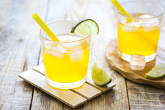 Sweet cocktails with lime and ice cubes on wooden tabel. Alcohol sweet cocktails for couple with lime and ice cubes on wooden tabel background Stock Image