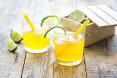 Sweet cocktails with lime and ice cubes on wooden tabel. Alcohol sweet cocktails for couple with lime and ice cubes on wooden tabel background Royalty Free Stock Images