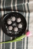 Sweet coconut balls in a dark plate with tulip on the table stock images