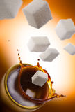 Sweet coffee. High angle view of sugar cubes falling into a cup of coffee Stock Image