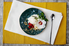 Sweet cold dessert and a white flower on a colorful table background. Vanilla ice cream with raspberries, mint and nuts. Royalty Free Stock Image